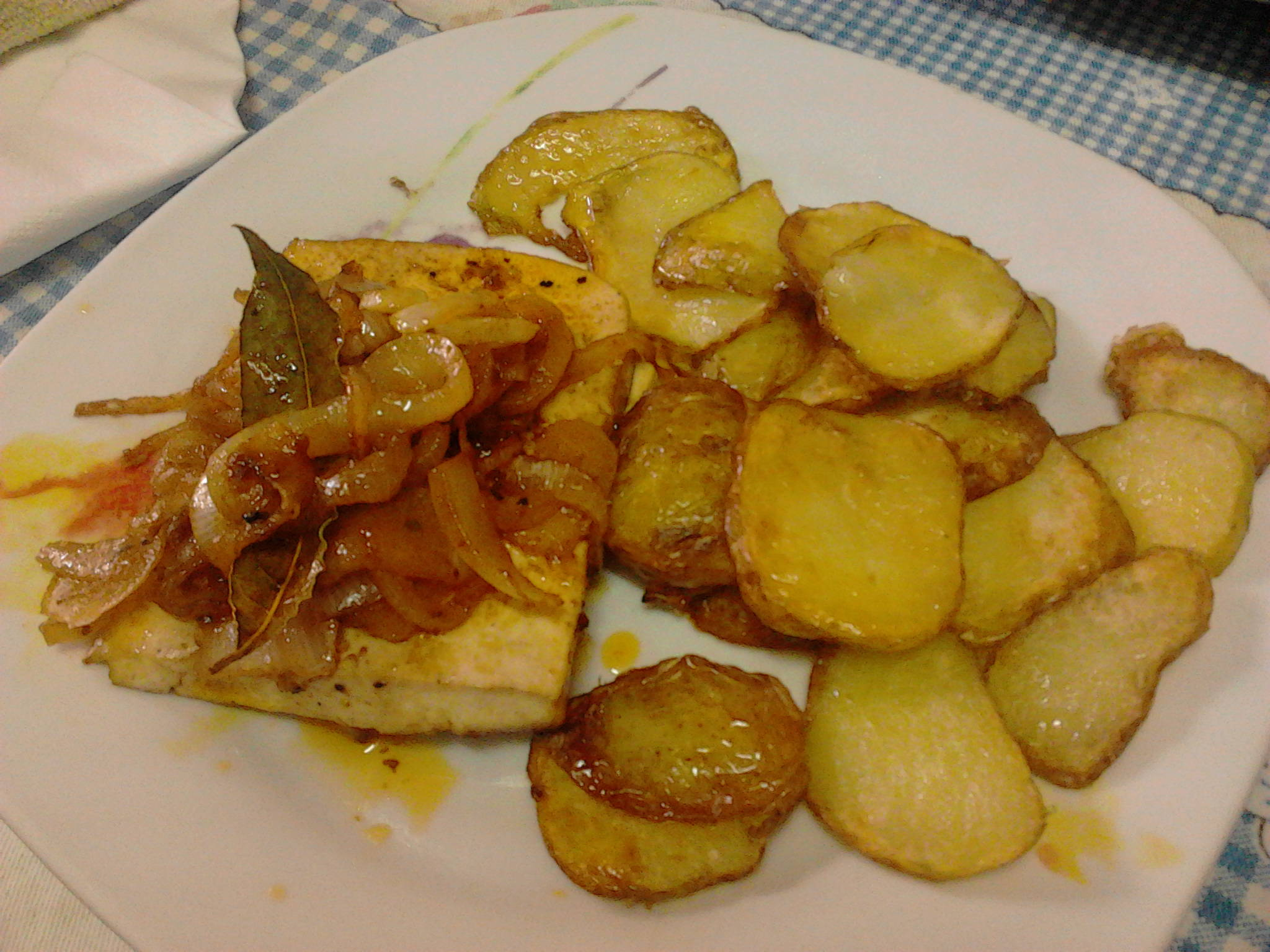 Tofu covered with onion and potatoes.